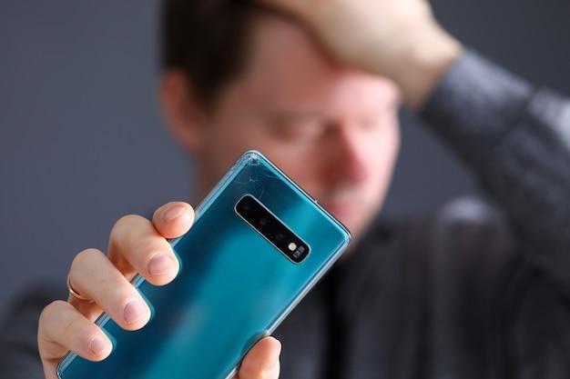 壊れた高価な現代のスマートフォンのクローズアップを手に持って物思いに沈んだ男