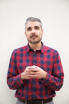 Pensive man holding smartphone and looking up