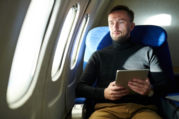 Pensive man holding tablet in airplane