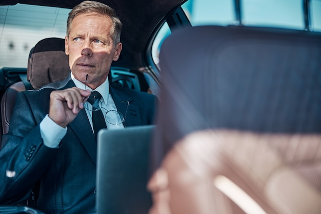 Задумчивый мужчина в элегантном костюме сидит на заднем сиденье машины и пользуется ноутбуком после приземления на самолет