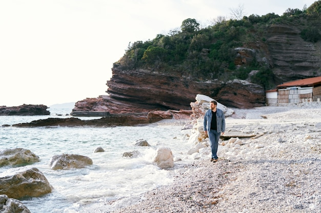 Pensive man in jeans and a denim jacket walks along a pebble beach looking at the water
