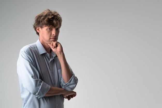 Задумчивый мужчина серьезно смотрит с кулаком на подбородке на светло-серой стене с копией пространства на правой стороне. фото высокого качества