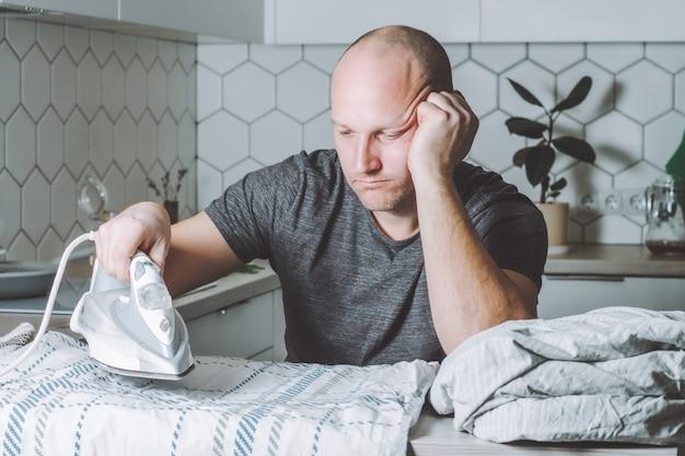 Задумчивый мужчина смотрит на утюг и постельное белье. отец занимается домашними делами.