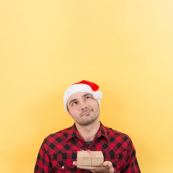 Pensive man in a red hat, holds a gift with interest on his face