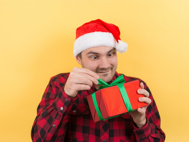 Pensive man in a red hat holds a gift with interest on his face