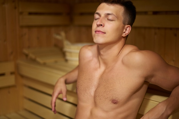 Pensive man relaxing in the steam sauna