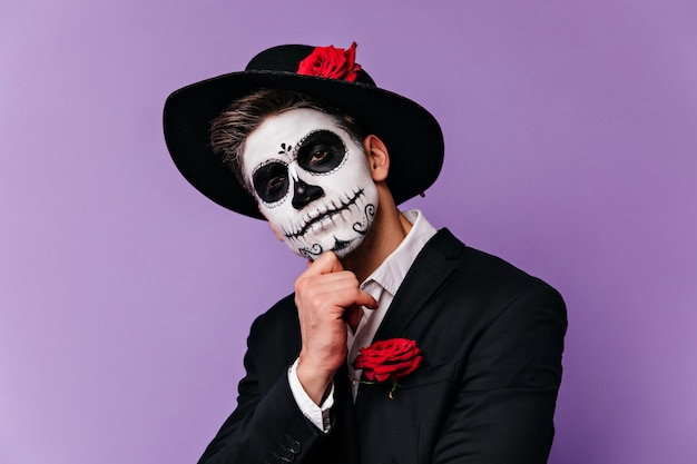 Pensive man in stylish black hat posing with scary party makeup. studio shot of handsome zombie boy isolated on bright background.