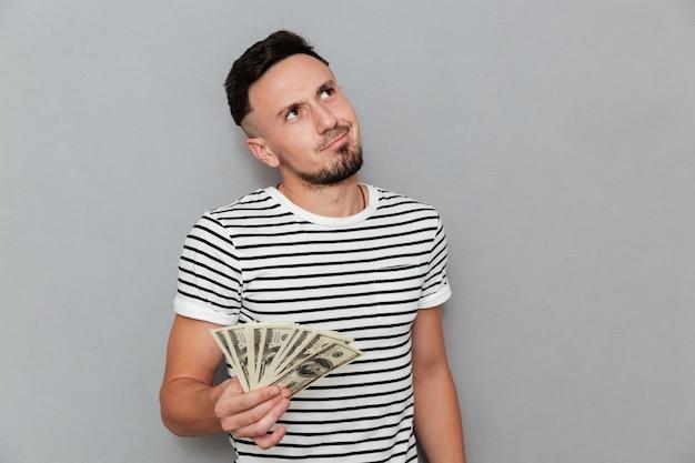 Uomo pensieroso in maglietta che tiene soldi e che osserva in su