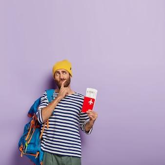 物思いにふける男の旅行者は、あごを持って、上向きに集中し、将来の海外旅行を計画し、搭乗券を飛ばしてパスポートを持って、リュックサックを運びます
