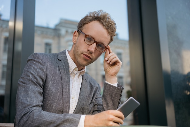 Pensive man using mobile phone looking at camera portrait of handsome manager wearing eyeglasses