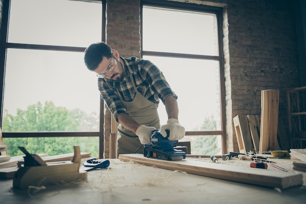 Pensive man wearing checkered shirt eye glasses protecting him from sawdust working by using sander