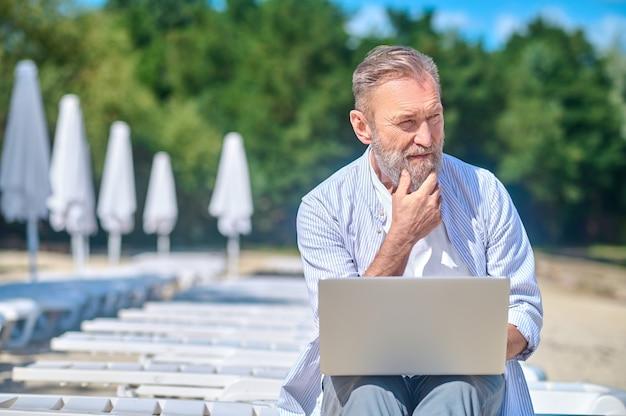 Задумчивый человек с ноутбуком, сидя на пляжном шезлонге