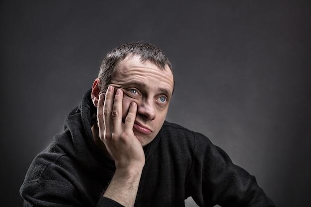 Задумчивый мужчина с ладонью на щеке думает над серым