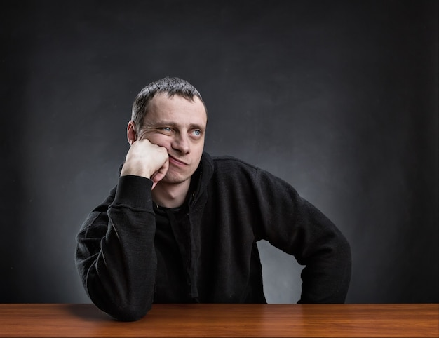 Задумчивый мужчина с ладонью на щеке думает
