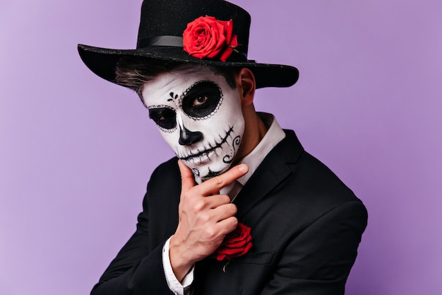 Pensive man with traditional mexican makeup looking to camera. studio shot of guy in zombie outfit posing before halloween party.
