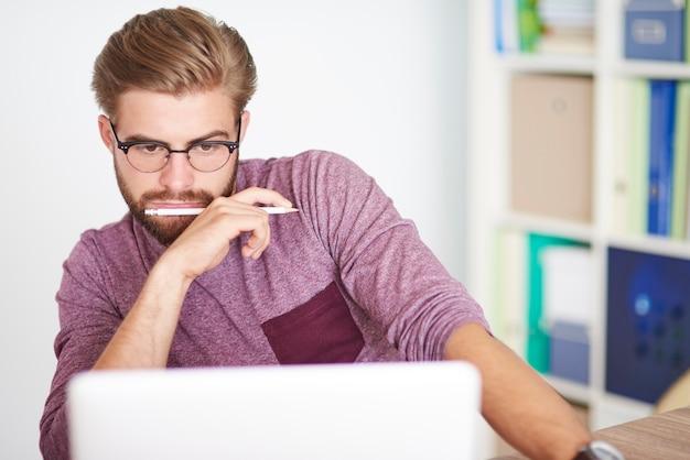 Задумчивый человек, работающий на ноутбуке