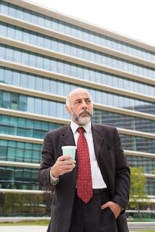 Задумчивый зрелый бизнесмен, держа бумажный стаканчик улицы