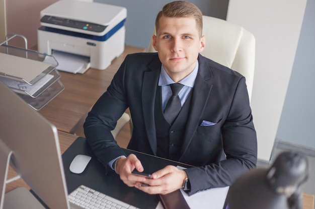 Pensive mature businessman looking up with concentration and writing in his paperwork at office