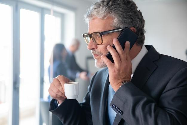 オフィスのガラスの壁のそばに立って携帯電話で話している間、小さなカップからエスプレッソをすすりながら物思いにふける成熟したビジネスマン。スペースをコピーします。ビジネスとコーヒーブレイクの概念