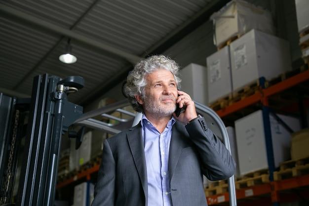 잠겨있는 성숙한 사업가 창고에서 지게차 근처에 서서 휴대 전화에 말하기. 배경에 상품이있는 선반. 비즈니스 또는 물류 개념