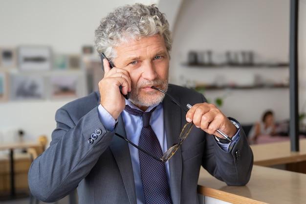 物思いにふける成熟したビジネスマンが携帯電話で話し、コワーキングに立って、机に寄りかかって、カメラを見て