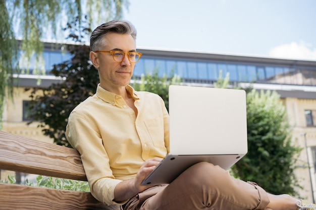 Pensive mature businessman using laptop, typing on keyboard