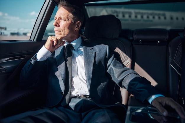 Задумчивый зрелый мужчина в элегантном костюме сидит на заднем сиденье после приземления самолета