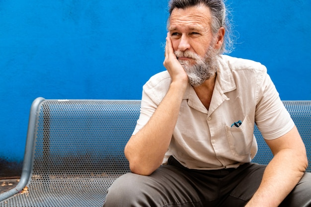 Pensive mature man with hand on face sitting on a bench sad and worried expression copy space