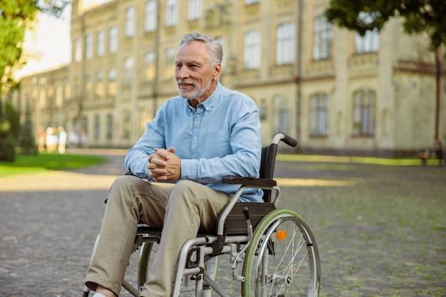 近くの公園で一人で時間を過ごしながら目をそらしている車椅子の物思いにふける成熟した回復中の男