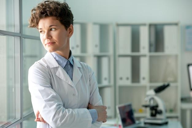 白衣を着た物思いにふける中年女性研究者が腕を組んで立ち、新しい実験を考えながら振り返る