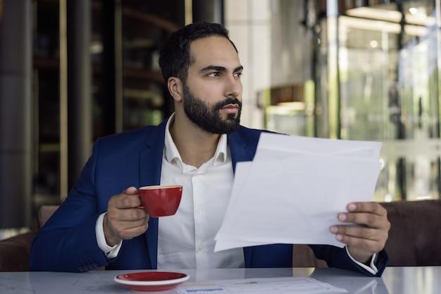 物思いにふける中東の実業家の読書契約、スタートアップの計画、コーヒーを飲む