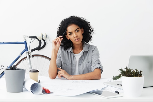 Pensive mixed race female student architect with black curly hair scratching head with pencil