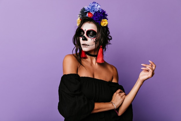 孤立した薄紫色の壁に大げさにポーズをとる珍しいフェイスアートの物思いにふけるモデル。