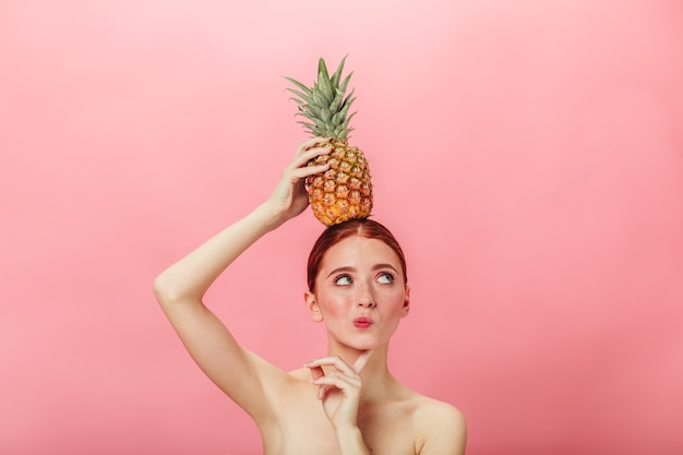 Pensive nude woman holding pineapple. ginger caucasian girl with exotic fruit and looking away.