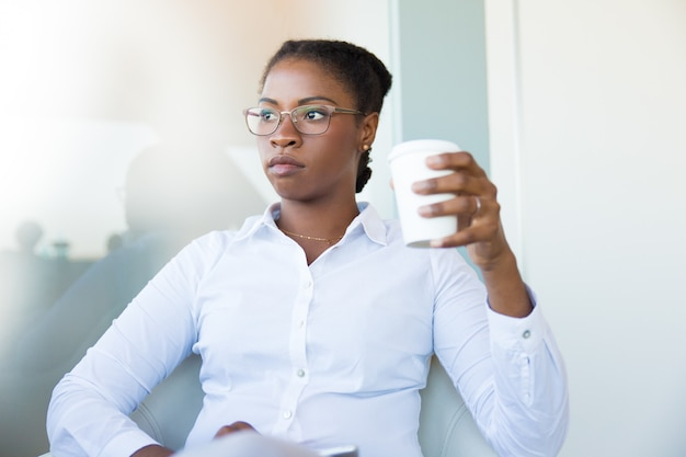 커피 브레이크를 즐기는 생각에 잠겨있는 사무실 직원