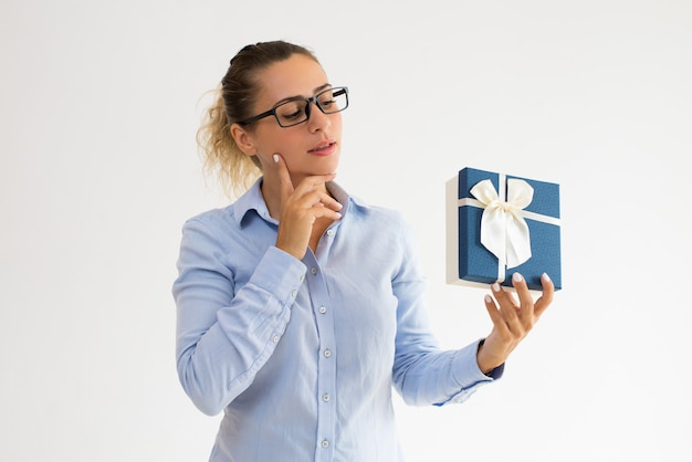 Pensive office girl in glasses guessing what in gift box
