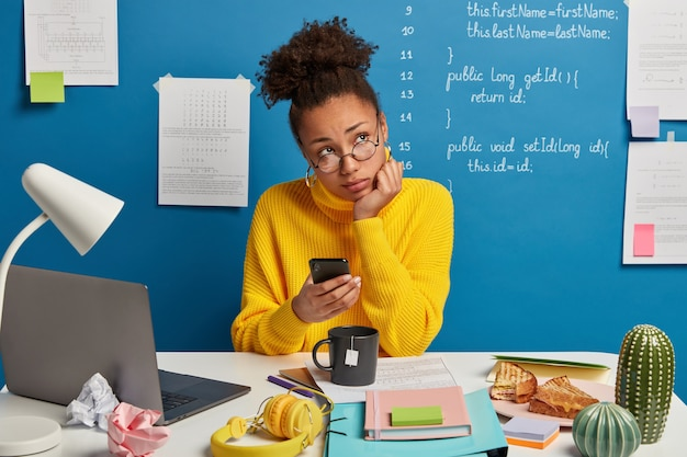 Pensive office worker thinks on creative idea, uses mobile phone, waits for call, prepares for course work, learns languages online, spends time for autodidact drinks tea wears yellow sweater