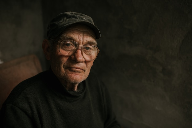 Задумчивый старик в очках с седыми волосами