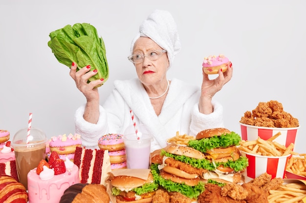 Pensive old woman chooses between healthy and unhealthy food holds green salad and tasty delicious donut