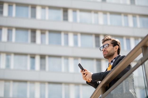 도시 환경에서 사무실 센터의 난간 옆에 서있는 스마트 폰으로 잠겨 있거나 영감을받은 젊은 밀레 니얼 세대