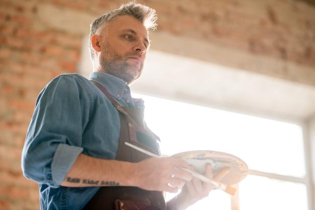 イーゼルの絵を見ながらアイデアを考えて作業服で物思いにふけるまたは深刻な中年男