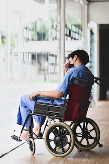 Pensive patient sitting on wheelchair feeling depressed and lonely.