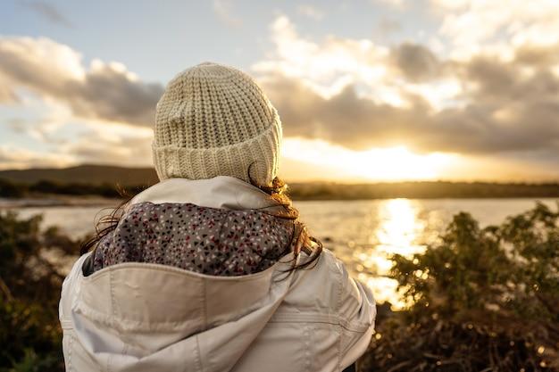 地平線を後ろから見た物思いにふける人。冬のウールのフード付きの服を着て後ろから見た認識できない女性は、海の上の雲と素晴らしい夕日や日の出を見ています