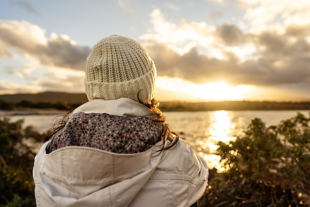 Pensive person view from back looking at the horizon. unrecognizable woman seen from behind dressed in winter wool hooded clothes looks at a wonderful sunset or sunrise with clouds over the sea