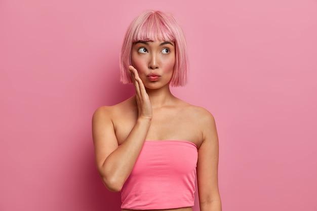 생각에 잠겨있는 분홍색 머리의 여성이 뺨을 만지고 위를 보며 무언가에 집중하고 캐주얼 한 탱크 탑을 입고 맨손으로 어깨를 보이며 트렌디 한 장밋빛 머리카락을 가졌습니다.