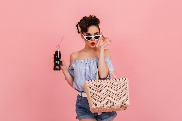 Задумчивая кинозвезды девушка с бутылкой газировки трогательно солнцезащитные очки. студия выстрел из изысканной элегантной женщины, изолированные на розовом фоне.