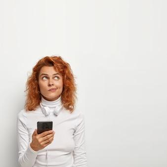 Задумчивая, симпатичная рыжая девушка держит смартфон, составляет плейлист с песнями, использует специальное приложение