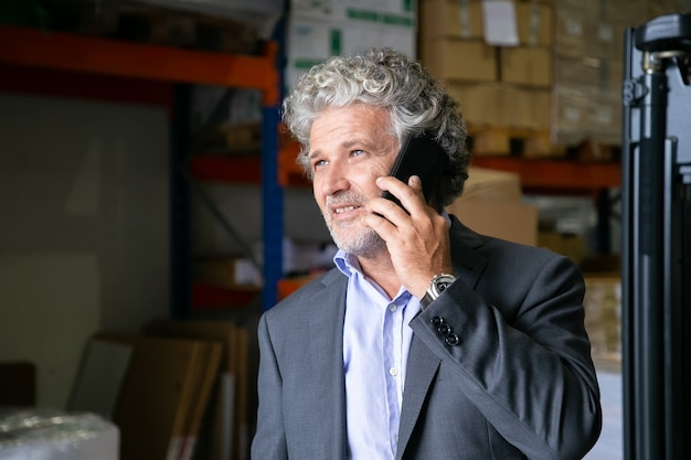 잠겨있는 긍정적 인 성숙한 기업가 창고에 서서 휴대 전화에 말하기. 배경에 상품이있는 선반. 공간을 복사하십시오. 비즈니스 또는 통신 개념