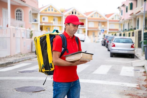 Задумчивый почтальон держит посылку и читает адрес в листе заказа. привлекательный доставщик в красной кепке и рубашке, стоя на открытом воздухе.