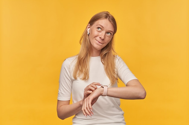 スマートウォッチを使用してワイヤレスイヤホンで音楽を聴き、黄色について考える白いtシャツのそばかすを持つ物思いにふけるきれいな女性